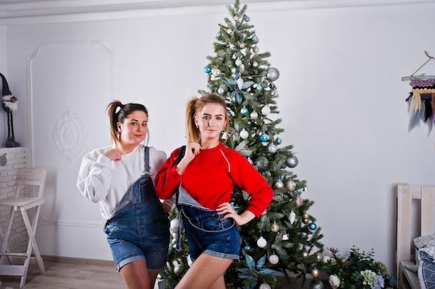 Due divertenti amici di belle ragazze indossano pantaloncini di jeans tuta e ghette contro l'albero di capodanno Foto Premium