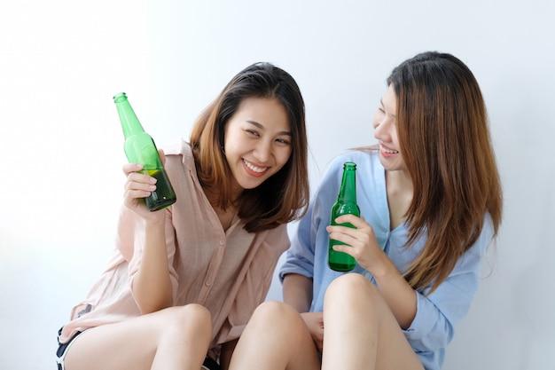 Due donne asiatiche che bevono birra al partito, celebrazione, coppia lgbt, stile di vita Foto Premium