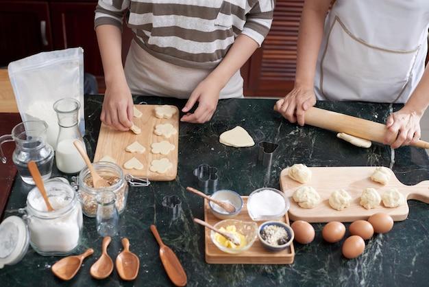 Due donne asiatiche irriconoscibili che rotolano pasta e che tagliano i biscotti sul contatore di cucina Foto Gratuite