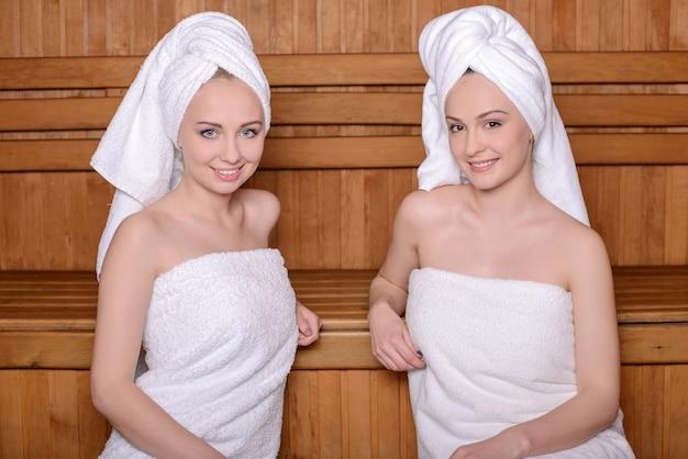 Due donne attraenti avvolte in un asciugamano rilassante nella sauna. Foto Premium