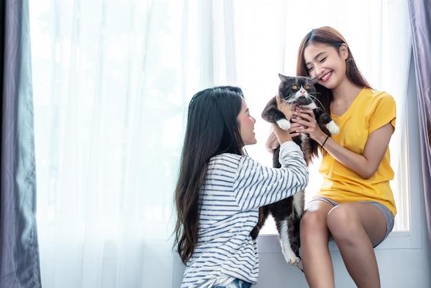 Due donne che trasportano e giocano con il gatto. stili di vita e concetto di persone Foto Premium