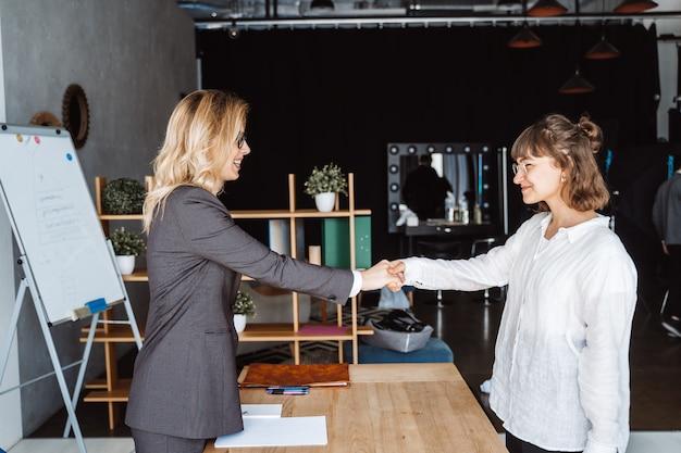 Due donne di affari che stringono le mani in ufficio Foto Gratuite