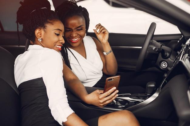 Due donne di colore alla moda in un salone di auto Foto Gratuite