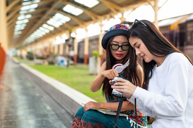 Due donne felici scattano foto mentre viaggiano alla stazione ferroviaria. concetto di turismo Foto Gratuite