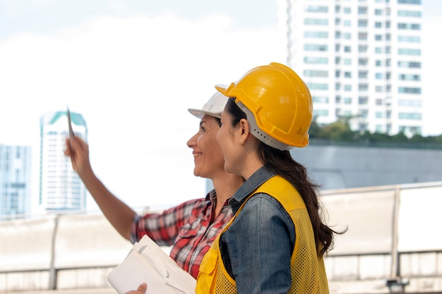 Due donne lavoratrici stanno lavorando insieme al cantiere Foto Premium
