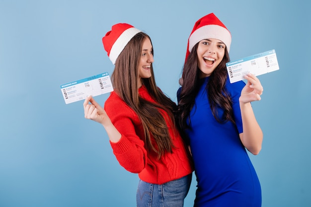 Due donne sorridenti che indossano i cappelli di santa con i biglietti aerei isolati sopra il blu Foto Premium