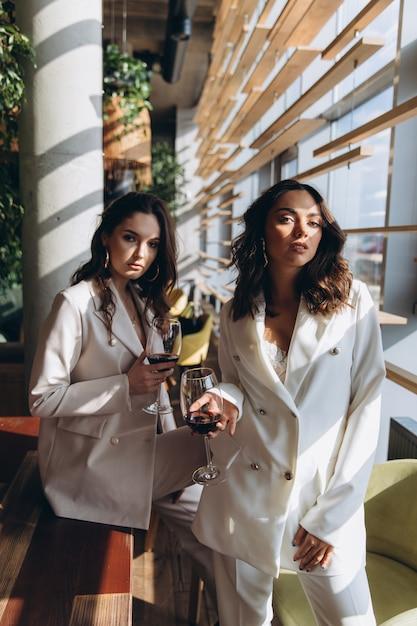 Due eleganti donne eleganti glamour sexy indossano abiti bianchi in un ristorante con un bicchiere di vino. Foto Premium