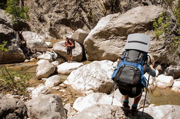 Due escursionisti che viaggiano attraverso il canyon con zaini Foto Premium