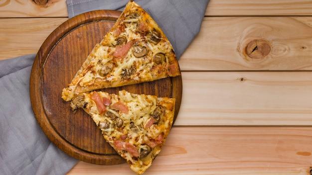 Due fette di pizza italiana formaggio sul vassoio di legno circolare sopra il tavolo Foto Gratuite