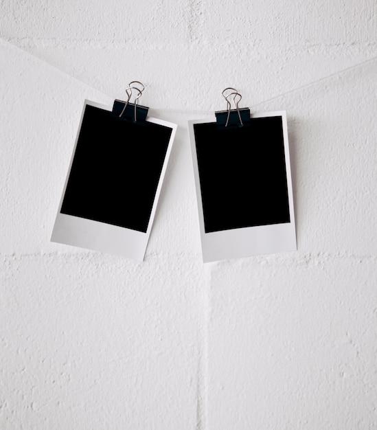 Due foto polaroid vuote attaccate alla stringa con le graffette del bulldog contro la parete Foto Gratuite