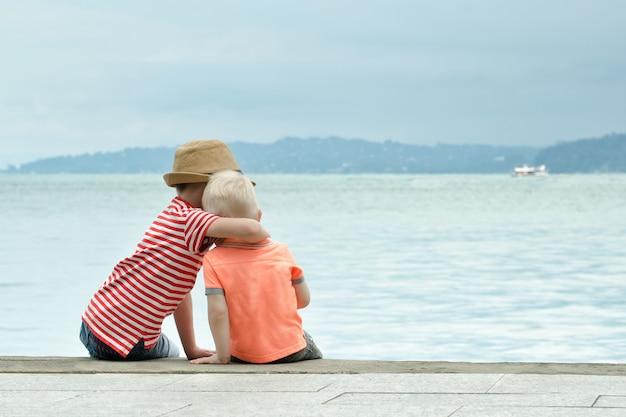 Due fratelli piccoli si siedono su un molo e si abbracciano contro il mare e le montagne in lontananza vista posteriore Foto Premium