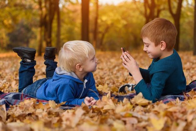 Due fratellini si fotografano l'un l'altro, sdraiati in foglie gialle autunnali. giorno d'autunno Foto Premium