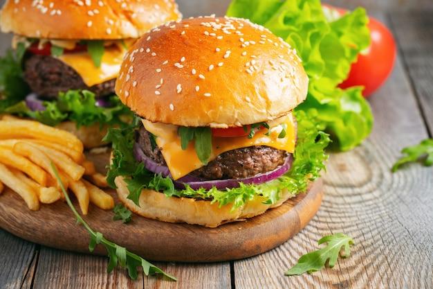 Due freschi hamburger fatti in casa con patate fritte su un tavolo di legno. Foto Premium
