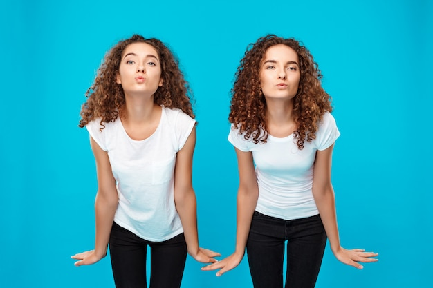 Due gemelli womans invio bacio, in posa sul blu. Foto Gratuite