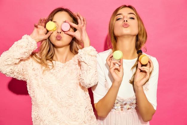 Due giovani affascinanti belle donne sorridenti hipster in abiti estivi alla moda. donne che producono occhiali, occhiali con amaretti colorati, che tengono macaron sul posto degli occhi. in posa sul muro rosa Foto Gratuite