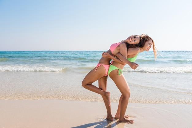 Due giovani asiatici brunch migliori amici guardando la fotocamera e ti mandano bacio d'aria, hanno corpo sottile sexy, indossando occhiali da sole bikini e gioielli luminosi di moda, in posa davanti alla spiaggia tropicale. Foto Gratuite
