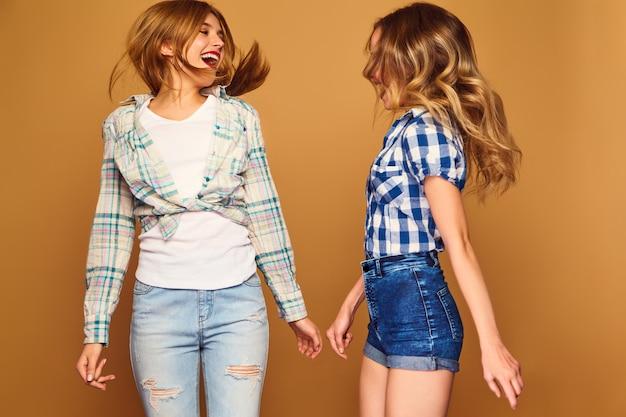 Due giovani bella bionda sorridente in camicie a scacchi estate alla moda Foto Gratuite