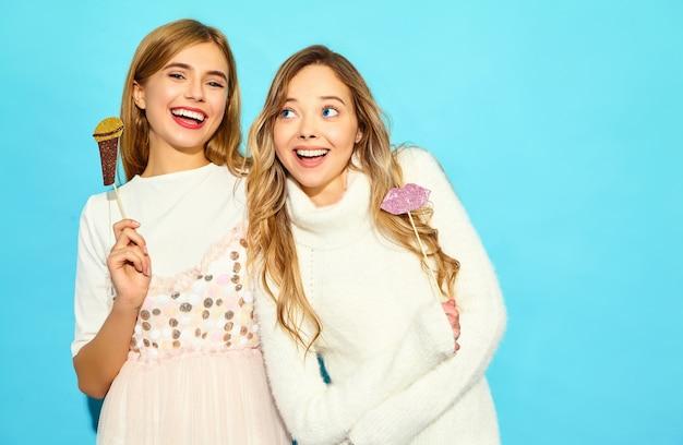 Due giovani belle donne che cantano con microfono falso puntelli. donne alla moda in abiti casual estivi. modelli divertenti isolati sulla parete blu Foto Gratuite