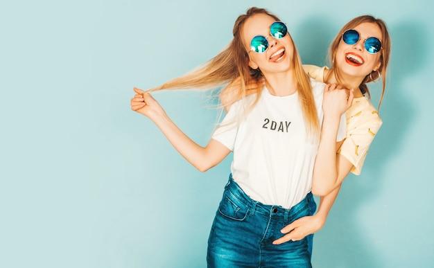 Due giovani belle ragazze bionde sorridenti dei pantaloni a vita bassa in gonne d'avanguardia dei jeans dell'estate vestiti. Foto Gratuite