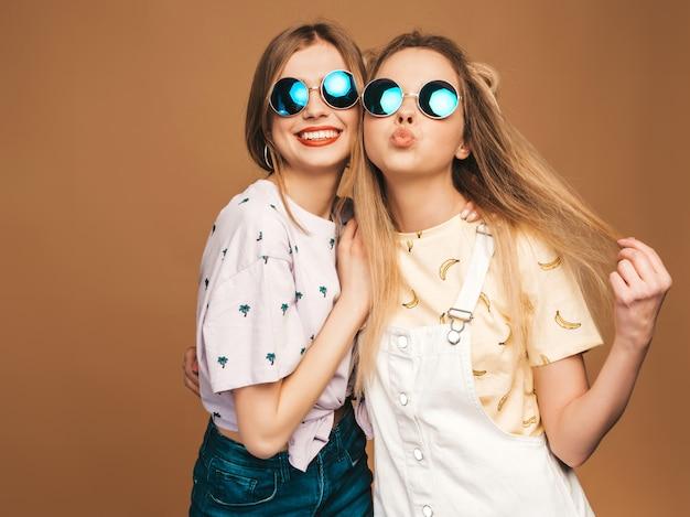 Due giovani belle ragazze bionde sorridenti dei pantaloni a vita bassa in vestiti variopinti della maglietta di estate alla moda. donne spensierate sexy che posano sul fondo beige in occhiali da sole rotondi. modelli positivi che si divertono Foto Gratuite