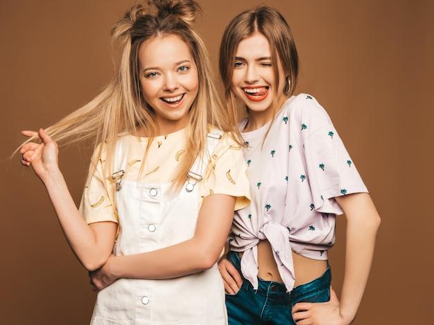 Due giovani belle ragazze bionde sorridenti dei pantaloni a vita bassa in vestiti variopinti della maglietta di estate alla moda. donne spensierate sexy che posano sul fondo beige. modelli positivi che si divertono Foto Gratuite