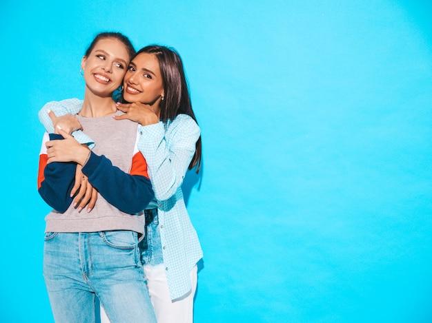Due giovani belle ragazze bionde sorridenti dei pantaloni a vita bassa in vestiti variopinti della maglietta di estate alla moda. donne spensierate sexy che posano vicino alla parete blu. modelli positivi che si divertono Foto Gratuite