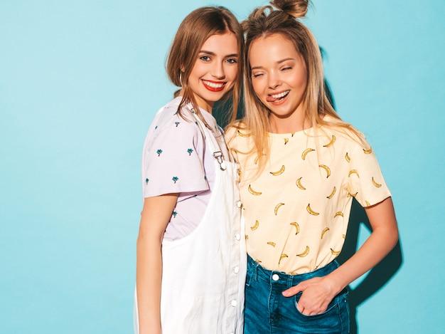 Due giovani belle ragazze bionde sorridenti dei pantaloni a vita bassa in vestiti variopinti della maglietta di estate alla moda. e mostrando la lingua Foto Gratuite