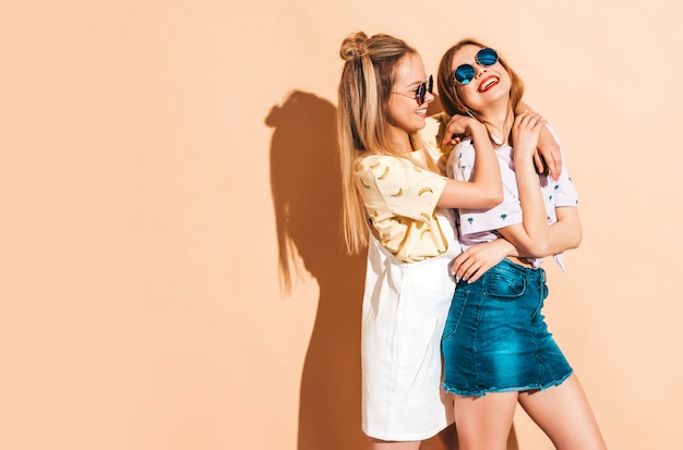Due giovani belle ragazze bionde sorridenti dei pantaloni a vita bassa in vestiti variopinti della maglietta di estate alla moda. Foto Gratuite