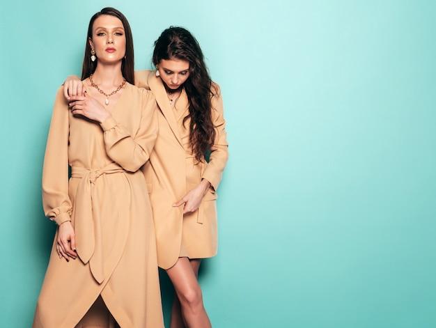 Due giovani belle ragazze castane in bei vestiti d'avanguardia di estate donne spensierate sexy che posano vicino alla parete blu in studio Foto Gratuite