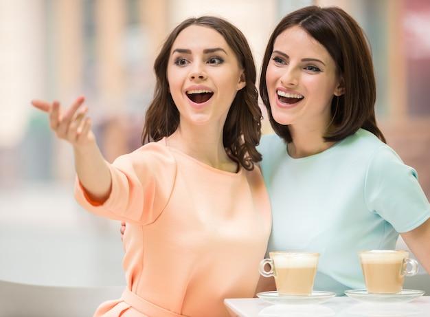 Due giovani belle ragazze che si siedono in caffè urbano con caffè. Foto Premium