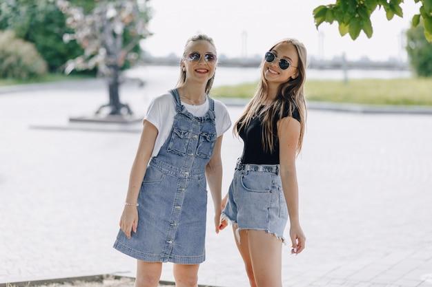 Due giovani belle ragazze in una passeggiata nel parco. una giornata di sole estivo, gioia e amicizie. Foto Gratuite