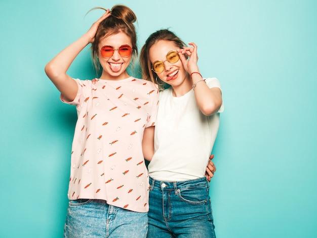 Due giovani belle ragazze sorridenti bionde dei pantaloni a vita bassa in vestiti d'avanguardia dei jeans dei pantaloni a vita bassa dell'estate. donne spensierate sexy che posano vicino alla parete blu. modelli trendy e positivi che si divertono con gli occhiali da sole Foto Gratuite