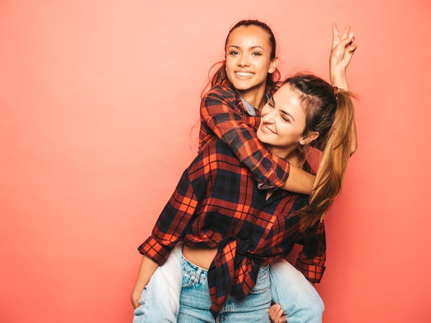 Due giovani belle ragazze sorridenti dei pantaloni a vita bassa del brunette in vestiti a quadretti simili d'avanguardia della camicia e dei jeans donne spensierate sexy che posano vicino alla parete rosa in studio modello positivo che si siede sulla sua parte posteriore dell'amico Foto Gratuite