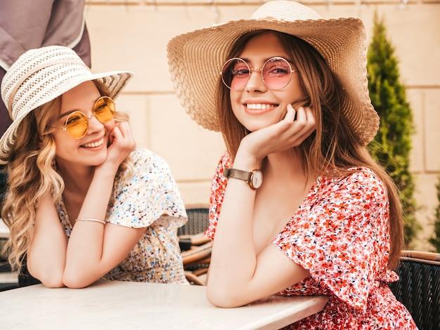 Due giovani belle ragazze sorridenti dei pantaloni a vita bassa in prendisole estive d'avanguardia donne libere che chiacchierano nel caffè della veranda sullo sfondo della strada in occhiali da sole modelli positivi divertendosi e comunicando Foto Gratuite