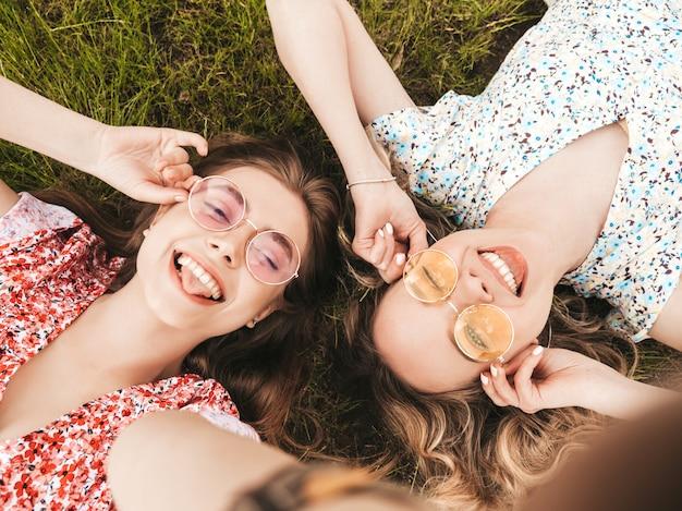 Due giovani belle ragazze sorridenti dei pantaloni a vita bassa in prendisole estive d'avanguardia donne spensierate sexy che si trovano sull'erba verde in occhiali da sole divertimento dei modelli positivi vista superiore scattare foto di selfie sullo smartphone Foto Gratuite