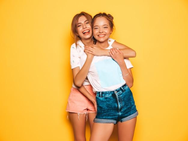Due giovani belle ragazze sorridenti hipster in abiti estivi alla moda. donne spensierate sexy che posano vicino alla parete gialla. modelle positive che impazziscono e si divertono Foto Gratuite