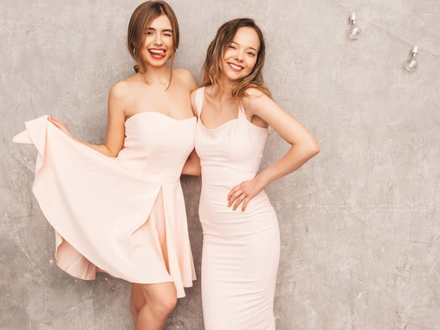 Due giovani belle ragazze sorridenti in abiti rosa chiaro alla moda estate. posa sexy spensierata delle donne. modelli positivi che si divertono Foto Gratuite