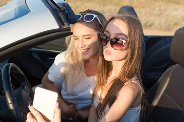 Due giovani donne attraenti in un'automobile del cabriolet Foto Premium