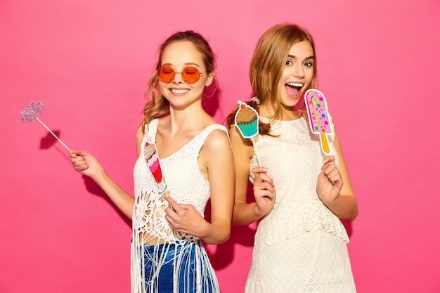 Due giovani donne bionde sorridenti alla moda che mangiano il gelato dolce degli oggetti di scena e il cocktail falso modelli positivi in vestiti dei pantaloni a vita bassa di estate che posano vicino alla parete rosa in occhiali da sole Foto Gratuite