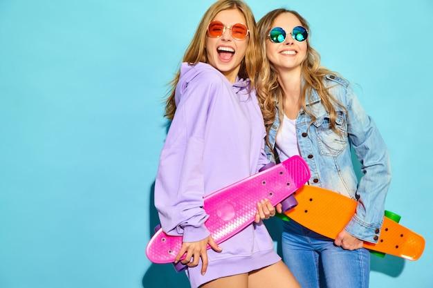 Due giovani donne bionde sorridenti alla moda con i pattini del penny. donne in abiti sportivi estate hipster in posa vicino al muro blu. modelli positivi Foto Gratuite
