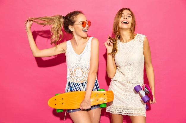 Due giovani donne bionde sorridenti alla moda con i pattini del penny. modelli in abiti bianchi hipster estate in posa vicino al muro rosa in occhiali da sole. femmina positiva Foto Gratuite