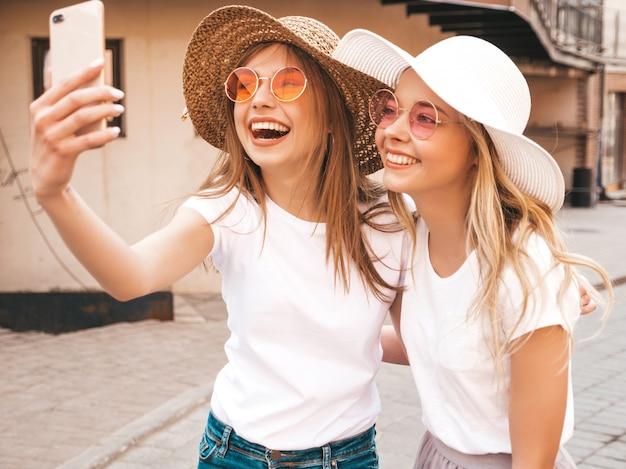 Due giovani donne bionde sorridenti dei pantaloni a vita bassa in vestiti bianchi della maglietta di estate. ragazze che prendono le foto dell'autoritratto del selfie sullo smartphone. Foto Gratuite