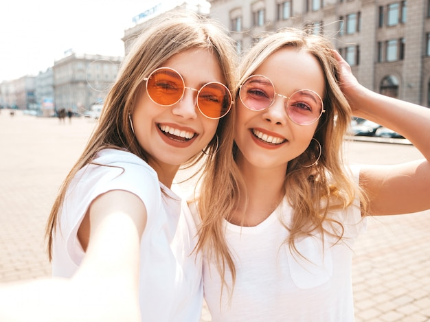 Due giovani donne bionde sorridenti dei pantaloni a vita bassa in vestiti bianchi della maglietta di estate. Foto Gratuite