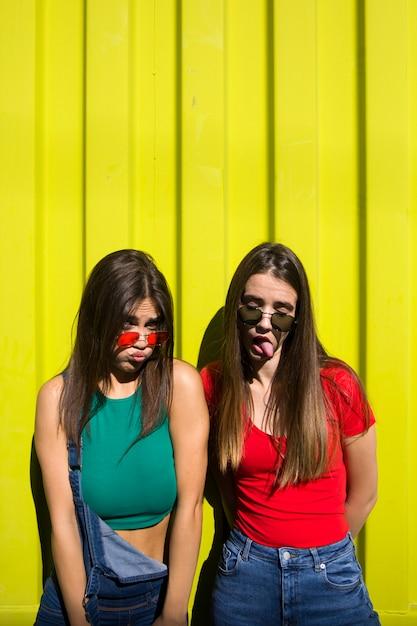 Due giovani donne casuali sveglie che imbrogliano davanti alla parete gialla Foto Premium
