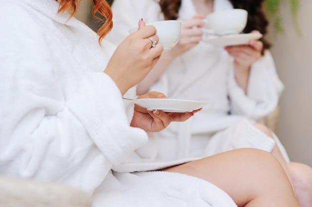 Due giovani donne che bevono tè dopo i trattamenti termali Foto Premium