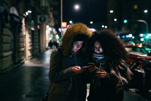 Due giovani donne che utilizzano smartphone Foto Premium