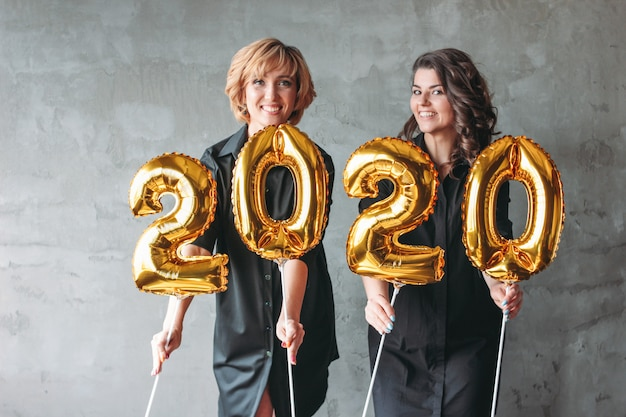 Due giovani donne in abiti neri in possesso dei palloncini numeri 2020 su sfondo grigio muro Foto Premium