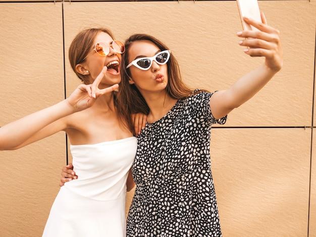 Due giovani donne sorridenti dei pantaloni a vita bassa in vestiti di estate. Foto Gratuite
