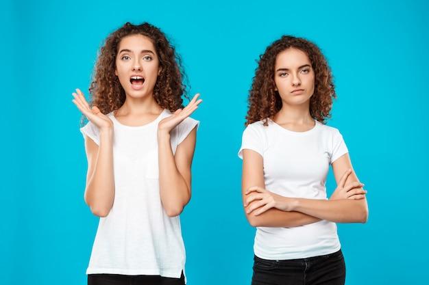 Due giovani gemelli womans in posa sul blu. Foto Gratuite