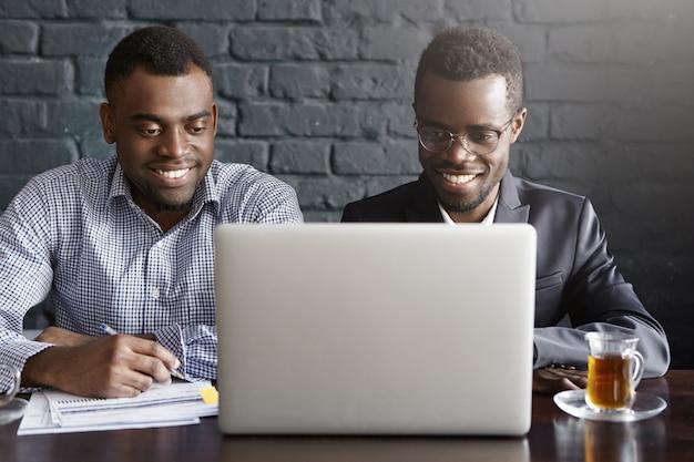 Due giovani imprenditori afroamericani di successo allegri che si siedono nell'interno moderno dell'ufficio davanti al computer portatile aperto, esaminando lo schermo con i sorrisi felici, discutendo i piani aziendali e le idee Foto Gratuite